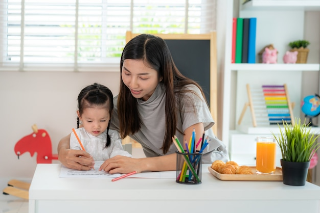 本の絵を描く母とアジアの女の子 Premium写真