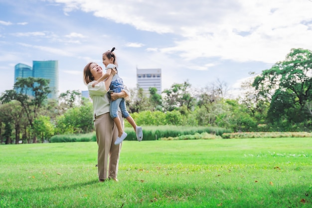 Asian grandmother and grandchildren having happy time together in park Premium Photo