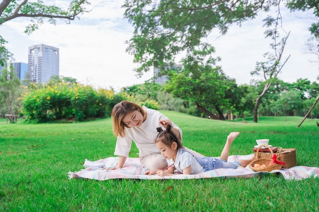 Asian grandmother and granddaughter laying on the green glass field outdoor, family enjoying picnic together in summer day Premium Photo