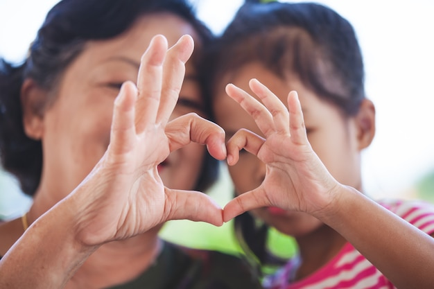 Asian grandmother and little child girl making heart shape with hands together with love Premium Photo