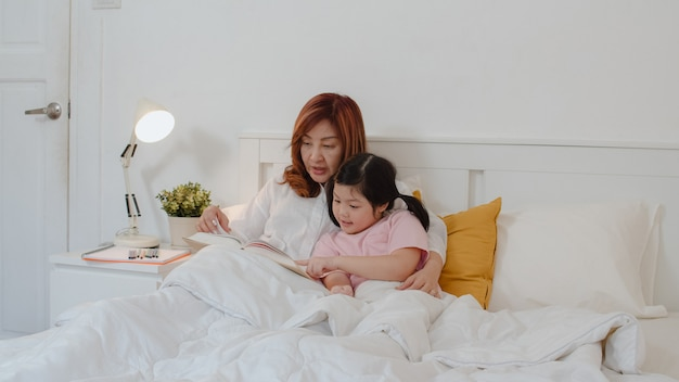 Asian grandmother read fairy tales to granddaughter at home. senior chinese, grandma happy relax with young girl enjoy good quality time lying on bed in bedroom at home at night concept. Free Photo