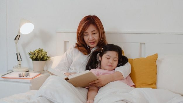 Asian grandmother read fairy tales to granddaughter at home. senior chinese, grandma happy relax with young girl who sleep while listening to tales lying on bed in bedroom at home at night concept. Free Photo