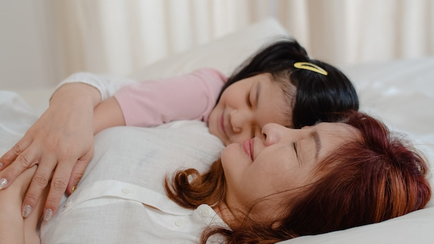 Asian grandmother sleep at home. senior chinese, grandma happy relax with young granddaughter girl kissing cheek for waking up lying on bed in bedroom at home at night concept. Free Photo