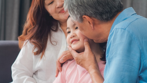 Asian grandparents kiss granddaughter cheek at home. senior chinese, old generation, grandfather and grandmother using family time relax with young girl kid lying on sofa in living room concept. Free Photo