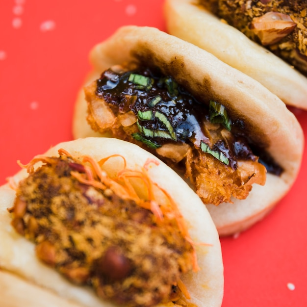 Asian gua bao with grilled chicken and teriyaki sauce on red backdrop Free Photo