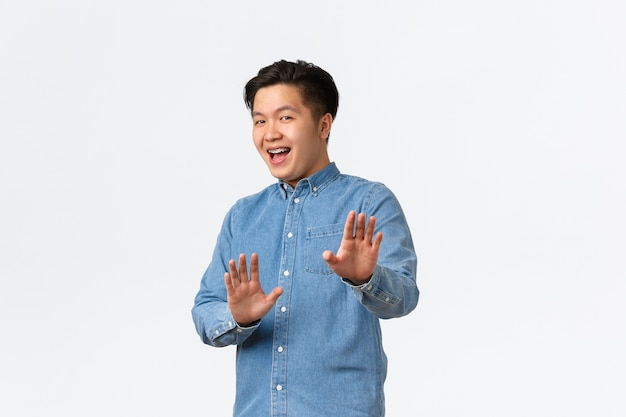 Asian guy feeling awkward, apologizing and step back, raising hands up in stop gesture, politely rejecting offer, saying no thank you, refusing something, smiling, standing white wall Free Photo