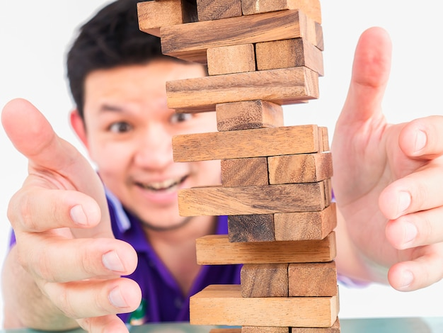 Asian guy is playing jenga, a wood blocks tower game Free Photo