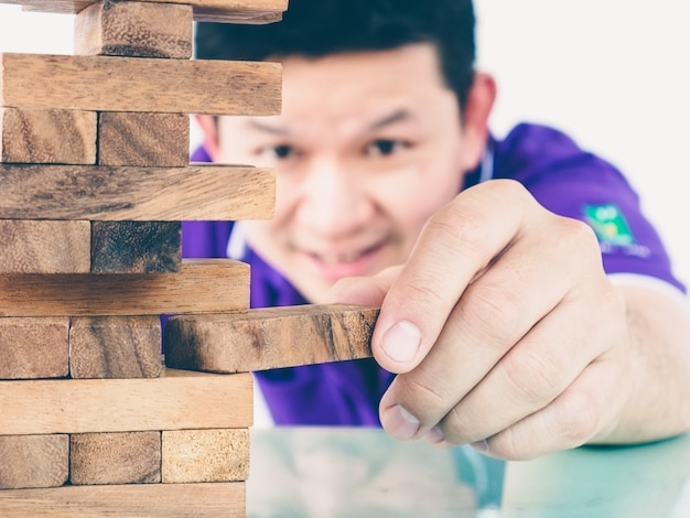 Asian guy is playing a wood blocks tower game for practicing physical and mental skill Free Photo