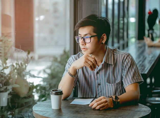Asian guy with glasses sitting and writing something with thought. Premium Photo