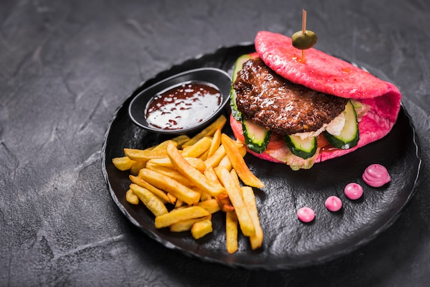 Asian hamburger with french fries and hot sauce Free Photo