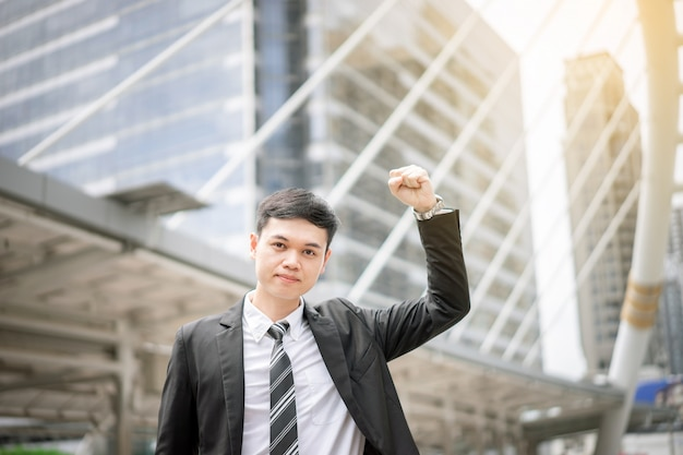 An asian handsome business man is very glad for his success. he is a manager who makes the increasing profit to the company Premium Photo