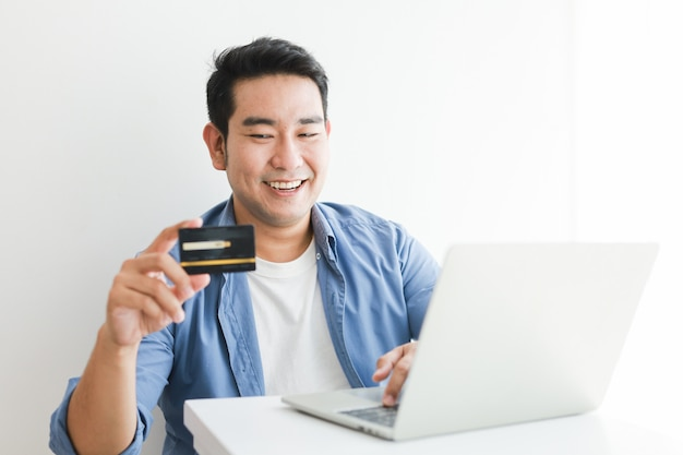 Asian handsome man in blue shirt using credit card with laptop computer shopping online Premium Photo
