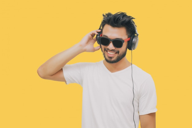 Asian handsome man with a mustache, smiling and laughing and using smart phone to listen music with headphones on yellow background Premium Photo