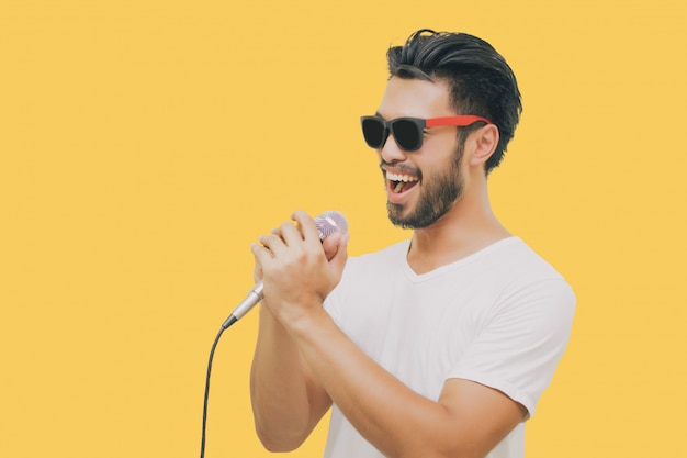 Asian handsome man with a mustache, smiling and singing to the microphone isolated on yellow background Premium Photo