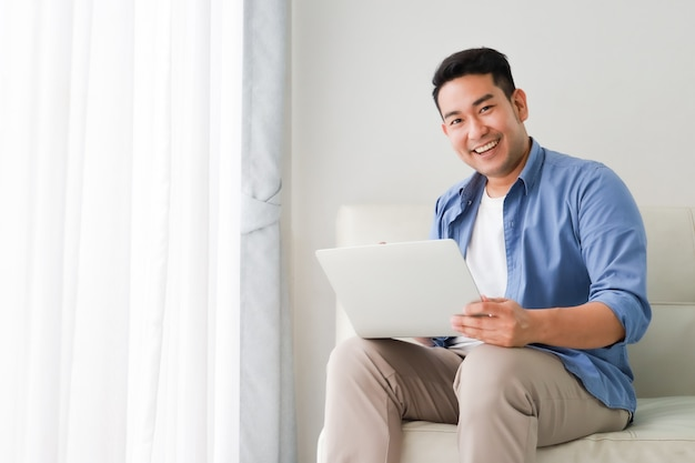 Asian handsome man working with laptop computer   in living room happy and smile face Premium Photo