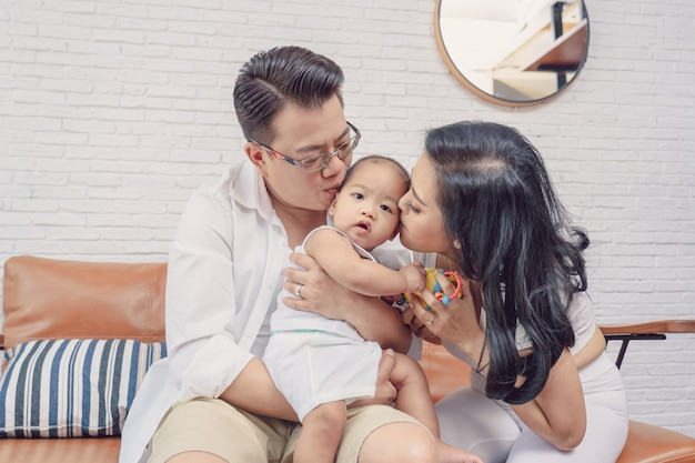 Asian happiness family scene of parent are kissing the boy baby in the living room of hous Premium Photo