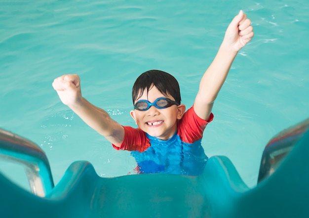 Asian happy kid playing slider in swimming pool Free Photo