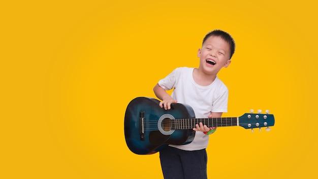 Азиатский счастливый улыбающийся 5-летний мальчик весело играет на гитаре, изолированные на цветном фоне Premium Фотографии
