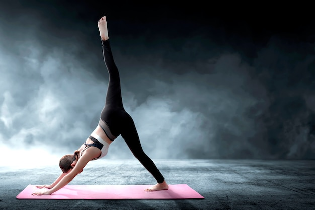 Asian healthy woman practicing yoga on the carpet at indoor Premium Photo