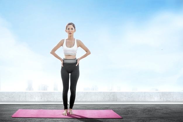 Asian healthy woman practicing yoga on the carpet at rooftop Premium Photo