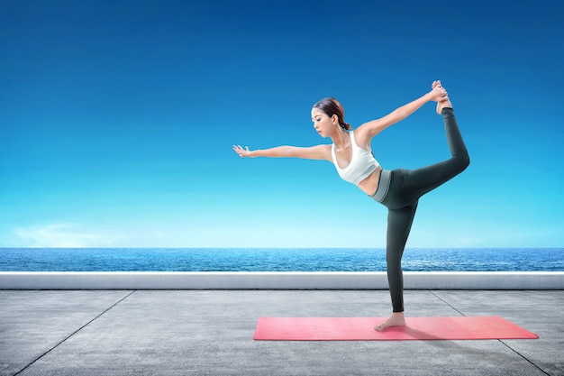 Asian healthy woman practicing yoga on the carpet at terrace Premium Photo