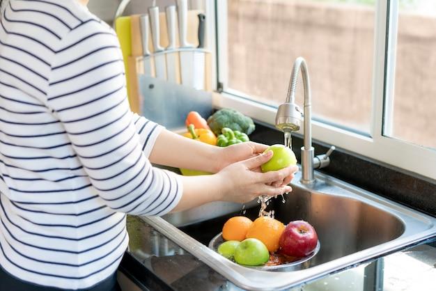アジアの健康な女性が台所の流しの上でリンゴや他の果物を洗い、汚染の可能性をなくすために果物/野菜を水で洗いますcovid-19。 Premium写真