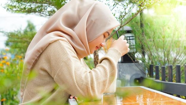 카페에서 마시는 아시아 Hijab 여자 프리미엄 사진