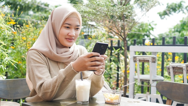 카페에서 전화를 재생 아시아 Hijab 여자 프리미엄 사진