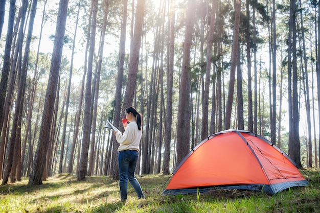 Asian hipster cute teen girl enjoying sunrise outside the tent. c&ing in forest. Premium & Asian hipster cute teen girl enjoying sunrise outside the tent ...