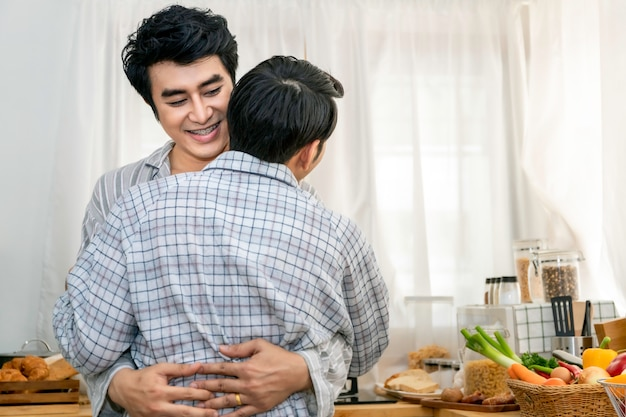 Asian homosexual couple hug and kiss at kitchen in the morning Premium Photo