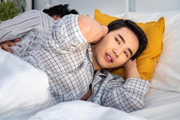 いびきをかくと寝室で寝ているパジャマ姿でアジアの同性愛カップル。彼は手で耳をブロック Premium写真