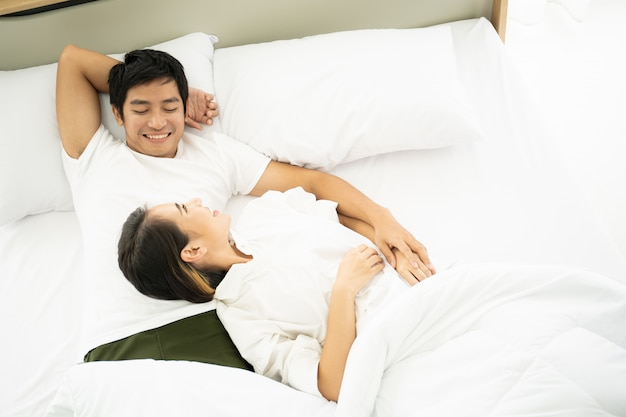 Asian husband and wife relaxing on the bed together in the morning. Premium Photo