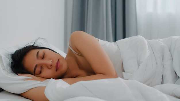 Asian indian lady sleep in room at home. young asian girl feeling happy relax rest lying on bed, feel comfortable and calm in bedroom at house at the morning. Free Photo