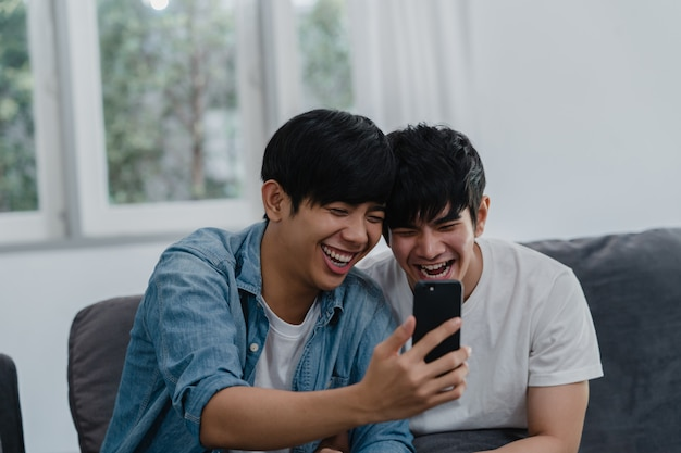 Asian influencer gay couple vlog at home. asian lgbtq men happy relax fun using technology mobile phone record lifestyle vlog video upload in social media while lying sofa in living room . Free Photo