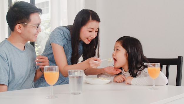 Asian japanese family has breakfast at home. asian happy dad, mom, and daughter eat spaghetti drink orange juice on table in modern kitchen at house in the morning . Free Photo