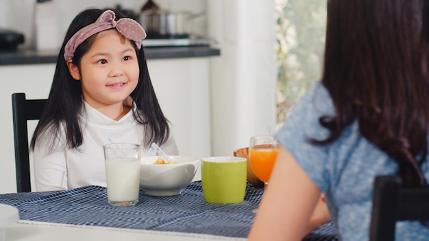 Asian japanese family has breakfast at home. asian mom, dad, and daughter feeling happy talking together while eat bread, corn flakes cereal and milk in bowl on table in the kitchen in the morning. Free Photo