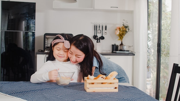 Asian japanese family has breakfast at home. asian mom and daughter feeling happy talking together while eat bread, corn flakes cereal and milk in bowl on table in modern kitchen at house in morning. Free Photo