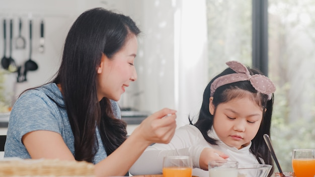Asian japanese family has breakfast at home. asian mom and daughter happy talking together while eating bread, drink orange juice, corn flakes cereal and milk on table in modern kitchen in morning. Free Photo
