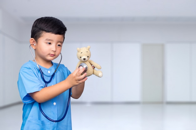 Asian kid in blue medical uniform with stethoscope Premium Photo