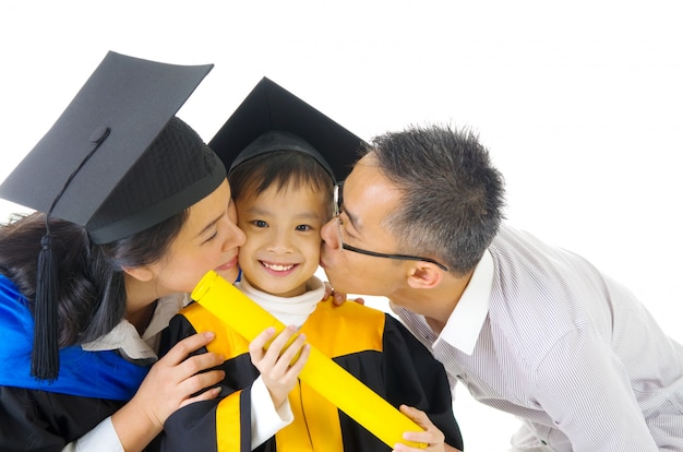 Asian kindergarten child in graduation gown and mortarboard kissed by her parent during graduation Premium Photo