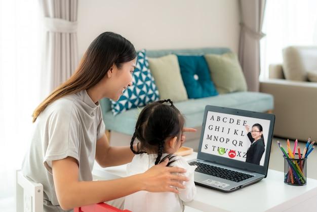 自宅のリビングルームのラップトップ上の教師と母のビデオ会議eラーニングとアジアの幼稚園の学校の女の子。ホームスクーリングと遠隔学習、オンライン、教育、インターネット。 Premium写真
