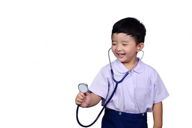 Asian kindergarten student kid playing medical stethoscope Premium Photo