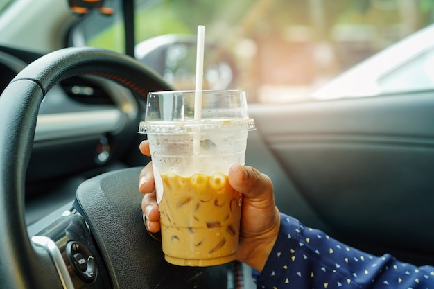 Asian lady holding ice coffee at car. Premium Photo
