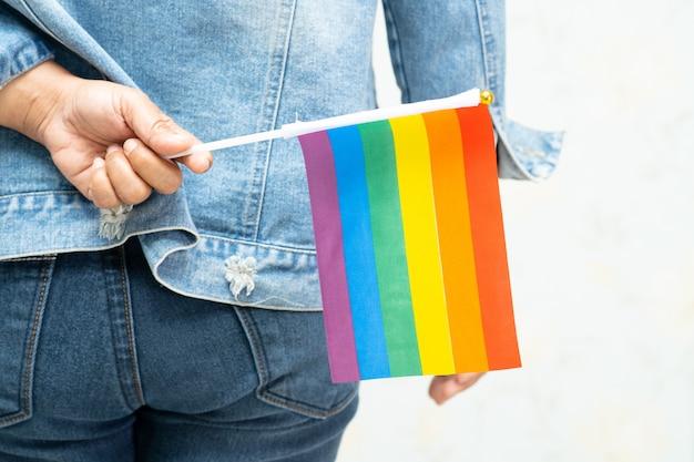 Азиатская дама в синей джинсовой куртке или джинсовой рубашке и держит флаг цвета радуги, символ месяца гордости лгбт. Premium Фотографии