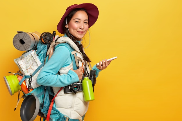 Asian lady with pleased expression, tries to find route with online navigation map, holds mobile phone, wears hat, casual clothes, carries rucksack, flask, binoculars, isolated on yellow wall Free Photo
