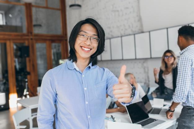 근무의 시작 부분에 엄지 손가락으로 포즈 아시아 웃는 소년. 블루 셔츠와 노트북으로 웃 고 안경에 중국 회사원. 무료 사진