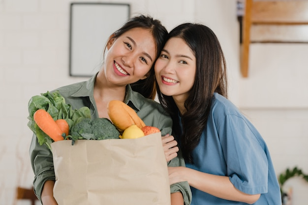 Asian lesbian lgbtq women couple hold grocery shopping paper bags at home Free Photo