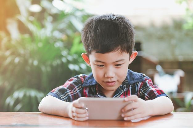 Азиатский мальчик сидит в онлайн-игре Premium Фотографии