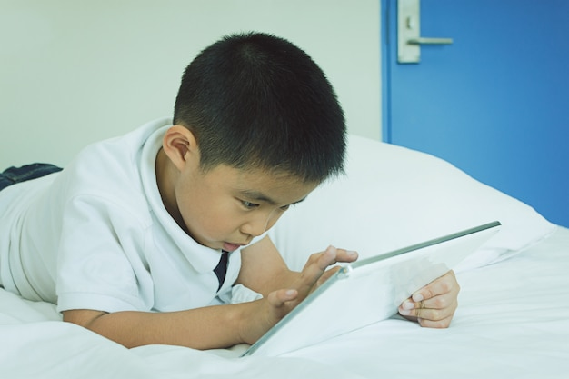 Asian little boy using tablet computer in bed Premium Photo