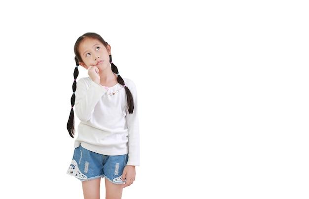 式を考えて、白い背景で隔離を見上げてアジアの小さな子供女の子。解決策のジェスチャーを見つけようとしている子供。 Premium写真
